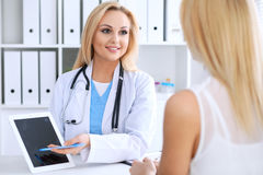 Doctor and  patient  discussing something while phisician pointing into laptop computer Royalty Free Stock Photo
