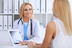 Doctor and  patient  discussing something while phisician pointing into laptop computer Stock Photos