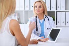 Doctor and  patient  discussing something while phisician pointing into laptop computer Royalty Free Stock Photography