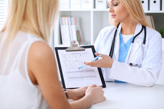 Doctor and  patient  discussing something while phisician pointing into medical history form at clipboard Stock Image