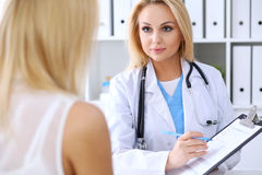 Doctor and  patient  discussing something while phisician pointing into medical history form at clipboard Stock Photography