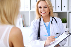 Doctor and  patient  discussing something while phisician pointing into medical history form at clipboard Royalty Free Stock Photos
