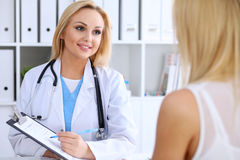 Doctor and  patient  discussing something while phisician pointing into medical history form at clipboard Stock Photos
