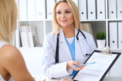 Doctor and  patient  discussing something while physician pointing into medical history form at clipboard Stock Photo