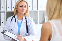 Doctor and  patient  discussing something while physician pointing into medical history form at clipboard Royalty Free Stock Image