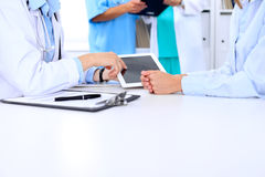 Doctor and patient are discussing something. Physician pointing into tablet computer. Royalty Free Stock Photos