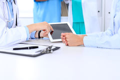 Doctor and patient are discussing something. Physician pointing into tablet computer. Stock Photography