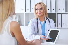 Doctor and patient discussing something while physician pointing into touch pad computer. Medicine and health care concept Royalty Free Stock Photo