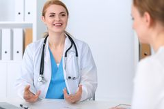 Doctor and patient are discussing something while sitting at the desk in hospital office, focus on cheerful smiling. Physician. Good news in medicine, health Stock Photo