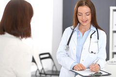 Doctor and patient discussing something while standing near reception desk in emergency hospital. Physician at work stock image