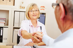 Doctor and patient doing handshake Stock Image