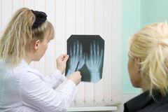 Doctor and patient examine x-ray of hands Royalty Free Stock Images