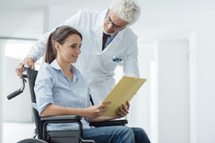 Doctor and patient examining medical records. Doctor and patient examining a file with medical records, she is sitting on a wheelchair, assistance and health Stock Photo