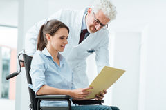 Doctor and patient examining medical records. Doctor and patient examining a file with medical records, she is sitting on a wheelchair, assistance and health Royalty Free Stock Images