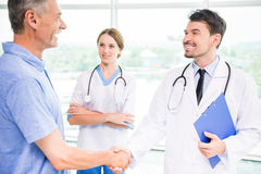 Doctor and patient. Happy male patient and his confident doctor shaking hands Stock Photo