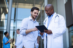 Doctor and patient having discussion on digital tablet Royalty Free Stock Images