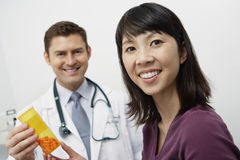 Doctor And Patient Holding Tablet Bottle Stock Photo