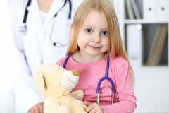 Doctor and patient in hospital. Child being examined by physician with stethoscope Royalty Free Stock Photo