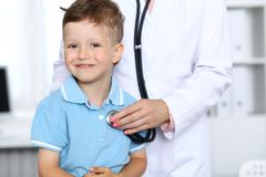 Doctor and patient in hospital. Happy little boy having fun while being examined with stethoscope. Healthcare and Stock Photography