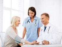 Doctor and patient in hospital. Healthcare and medical concept - doctor and nurse with patient measuring blood pressure Stock Images