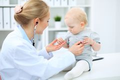 Doctor and patient in hospital. Little girl is being examined by pediatrician with stethoscope. Medicine and health care.  stock image