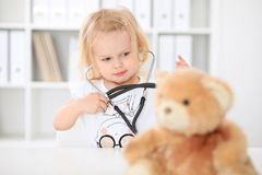 Doctor and patient in hospital. Little girl examining teddy bear with stethoscope. Health care, insurance and help stock photography