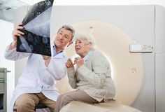 Doctor And Patient Looking At CT Scan X-ray. Mature male radiologist explaining CT Scan to an elderly female patient Royalty Free Stock Images