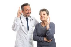Doctor and patient making revelation gesture. Smiling doctor and female patient making revelation gesture and expression with index finger as understanding stock images