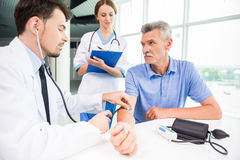 Doctor and patient. Male medical doctor examining his mature patient with stethoscope Royalty Free Stock Photos