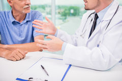 Doctor and patient. Male doctor talking with patient seriously at clinic. Close-up Royalty Free Stock Image