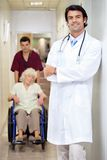 Doctor With Patient And Male Technician. Portrait of doctor standing arms crossed with male technician and patient in background Stock Photography