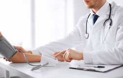 Doctor and patient measuring blood pressure. Healthcare, hospital and medicine concept - doctor and patient measuring blood pressure royalty free stock photo