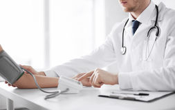 Doctor and patient measuring blood pressure Stock Photos