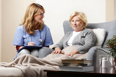 Doctor and patient. Portrait of female doctor talking to her senior patient while sitting at nursing home Royalty Free Stock Image