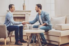 Positive nice men shaking hands. Doctor and patient. Positive nice men shaking hands while greeting each other stock photography