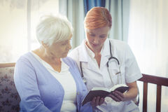 Doctor and patient reading a book. At home Royalty Free Stock Photos