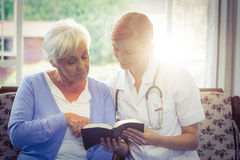 Doctor and patient reading a book. At home Stock Photos