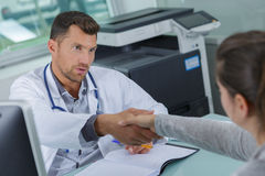 Doctor and patient shaking hands Stock Photos