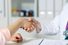 Doctor and patient shaking hands. Female doctor shaking hands with patient. Partnership, trust and medical ethics concept. Handshake with satisfied client Stock Photography
