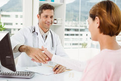 Doctor and patient shaking hands in medical office Royalty Free Stock Photo