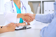 Doctor and patient are shaking hands Stock Image