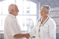 Doctor and patient shaking hands smiling. Senior female doctor and male patient shaking hands, smiling Royalty Free Stock Photo
