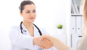Doctor and patient shaking hands to each other. Healthcare, medicine and trusting concept. Stock Image