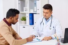 Doctor and patient signing document at clinic. Medicine, healthcare and people concept - doctor with clipboard and young male patient signing medical document at royalty free stock image