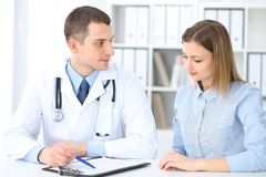 Doctor and patient sitting at the desk. Medicine and health care concept royalty free stock photography