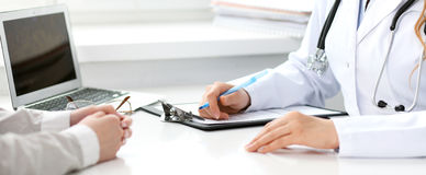 Doctor and  patient  sitting at the desk Stock Photos