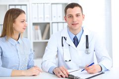 Doctor and  patient  sitting at the desk. Medicine and health care concept Royalty Free Stock Photo