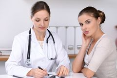 Doctor and  patient  sitting at the desk. The physician or therapist makes a diagnosis. Health care, medicine and patie Royalty Free Stock Photo