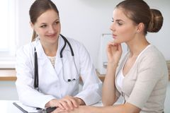 Doctor and  patient  sitting at the desk. The physician or therapist makes a diagnosis. Health care, medicine and patie. Nt service concept Stock Photography