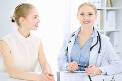 Doctor and patient talking in hospital office while sitting at the desk. Health care and client service in medicine royalty free stock image